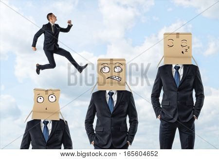 Small businessman jumping over three men in suits who are wearing carton boxes with painted faces. Business and success. Business hierarchy. Corporate ladder.
