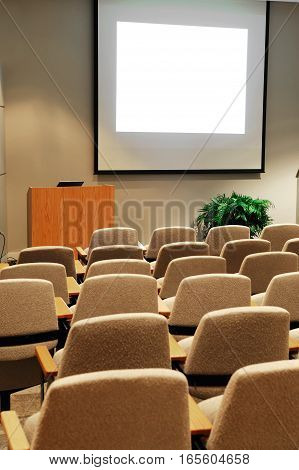 close up on auditorium room with projector screen and rows of seats
