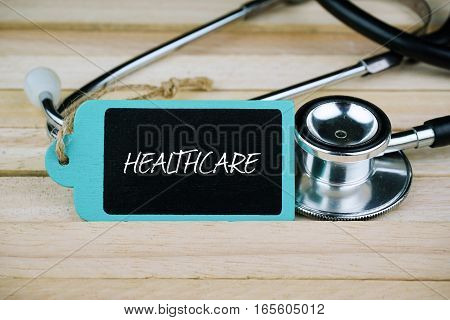 Wooden tag written with Healthcare and stethoscope on wooden background. Medical and Healthcare concept.
