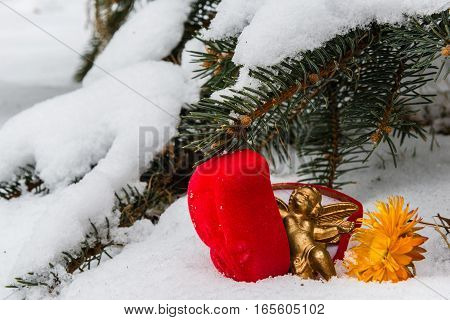 Red box for wedding ring with gold color angel figure and yellow dry flower in the snow against the background of snow-covered fir branches