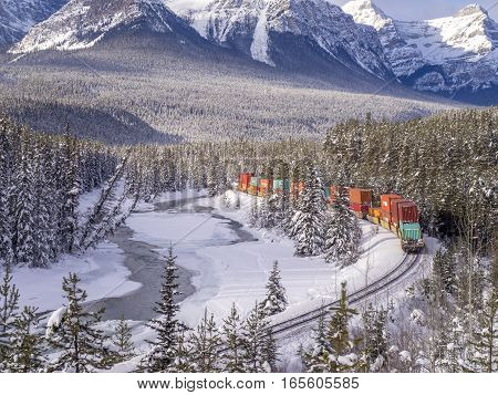 BANFF, ALBERTA - JAN 15: Train on Morant's Curve on January 15, 2017 iin Banff National Park, Alberta, Canada. Morant's Curve is a scenic spot 4 kilometers east of Lake Louise on the old Highway.