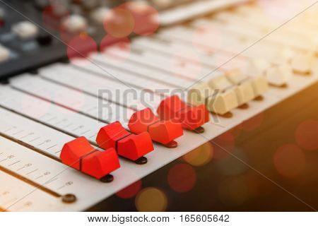 Close up of red audio sound mixer and buttons with bokeh background.