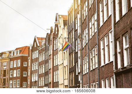 Multi-colored flags on a house in Amsterdam in the Netherlands. European sexual revolution.