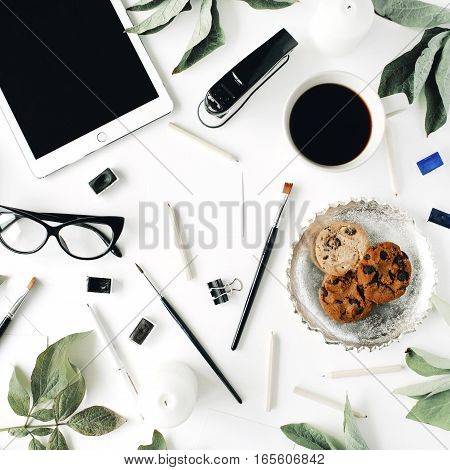 Workspace with tablet glasses cup of black coffee cookies on golden tray pencils paintbrushes and leaves. Flat lay composition for blog. Top view.