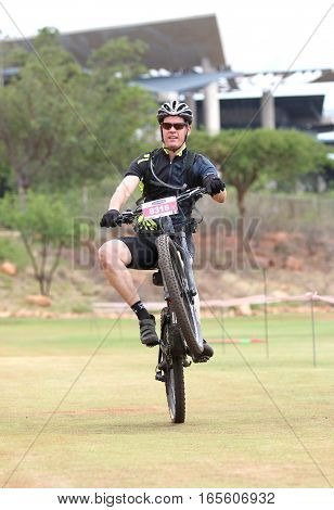 Happy Middle Aged Man Popping Wheelie At The Finish Line At Mountain Bike Race