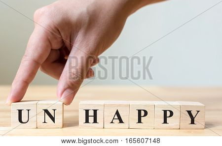 The words of unhappy on wood blocks business concept