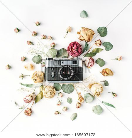 Flat lay top view vintage retro photo camera beige roses and green leaves on white. Blog hero