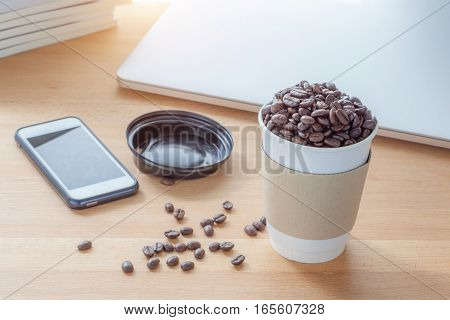 Start working day with the cup of roasted aroma coffee beans and blurred background of work place laptop and smart phone.