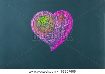 Heart symbol drawn with chalk colors on green board. Happy valentines day concept. Background for copy texts or graphic components.