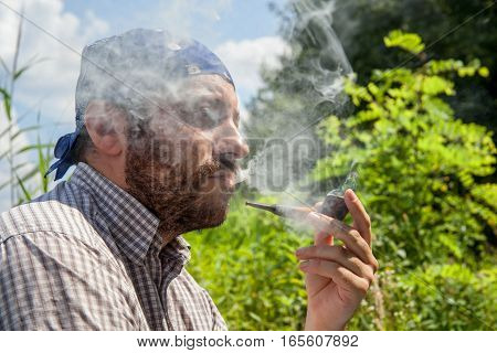 Bearded man enjoying his pipe and releasing smoke outside on a summer day