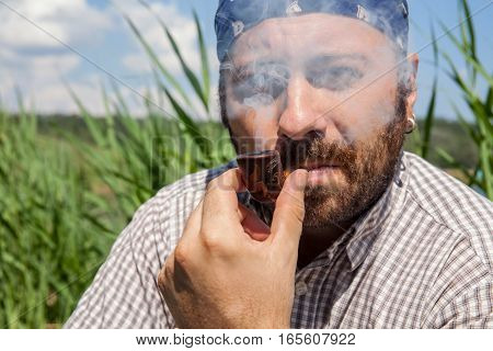 Bearded man smoking his pipe outside on a summer day