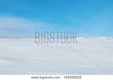 Winter landscape with snow covered desolate hill and field. Bright clear blue sky and isolated white cloud over hill top.