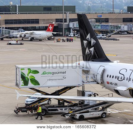 Kloten, Switzerland - 5 August, 2015: a truck of Gate Gourmet at an Airbus A320-214 of Star Alliance in the Zurich Airport. Gate Gourmet is a leading global provider of airline catering and provisioning services.