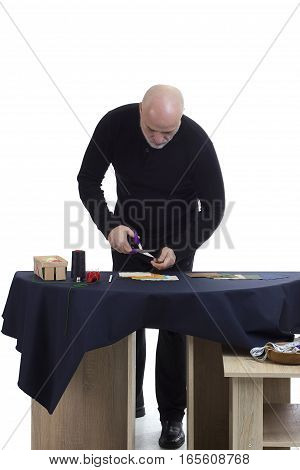 Mature tailor at work on a white background