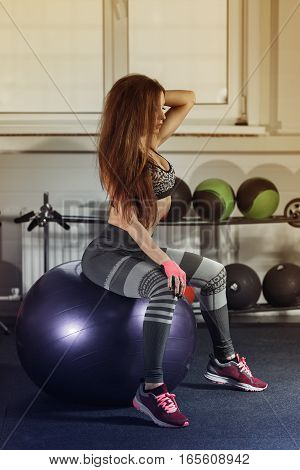 Young Sexy Woman Sit On Fitness Ball In Gym.