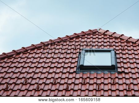 Attic skylight window on red ceramic tiles house roof outdoor. Attic Skylights Home Design Ideas Exterior. Roofing Construction.