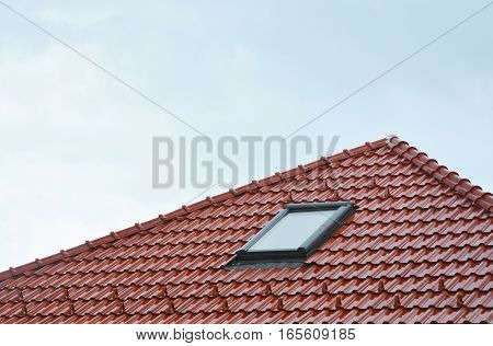 Beautiful house roof window sun tunnel skylights or skylight after rain on red ceramic clay roof tiles. Attic skylight solution outdoor.