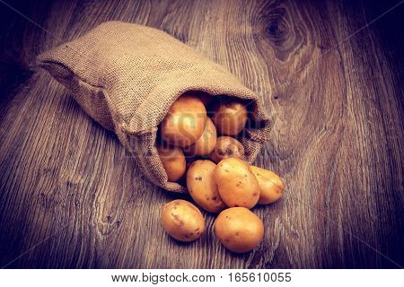 Raw potatoes in the sack on wooden background. Toned image