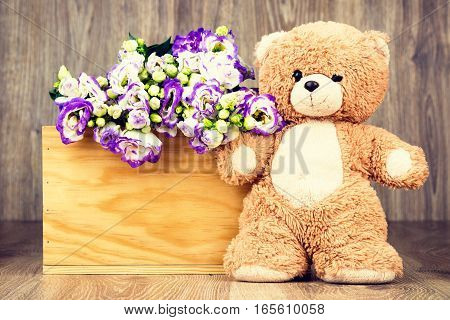 Bunch of flowers and a teddy bear on wooden background.Toned image