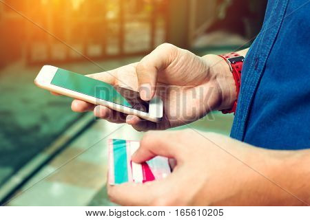 Man Use Smart Phone And Holding Credit Card. Online Payment Concept.
