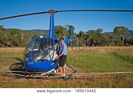 Helicopter and pilot get ready to fly map land