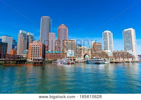 Boston cityscape reflected in water, skyscrapers and office buildings in downtown against the clear blue sky, view from Boston harbor, USA