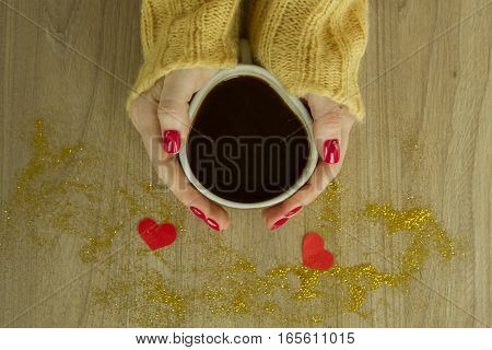 Cup of coffee or tea in womans's hands with good red manicure in knitted sweater