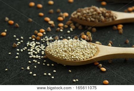 Two wood spoon with quinoa and buckwheat on black background