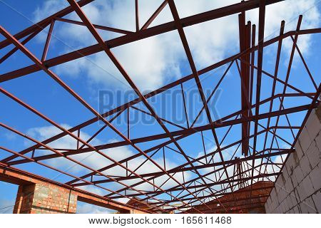 Steel roof trusses details with clouds sky background. Steel roof trusses sitting on concrete pole view from inside home factory.