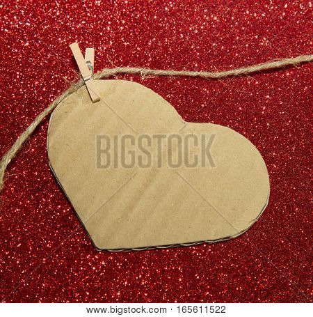 One carton heart attached to the rope on shining background
