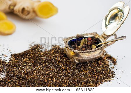 dry masala tea leaves scattered with spices in the vintage bowl and ginger white background target focus