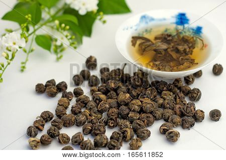 Dry leaves of jasmine green tea scattered on the white table and brewed in the china cup with flowers on the background