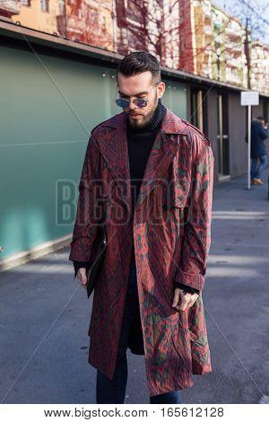 MILAN ITALY - JANUARY 16: Fashionable man poses outside Etro fashion show building during Milan Men's Fashion Week on JANUARY 16 2017 in Milan.