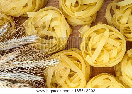 Pasta tagliatelle in the form of nests on a cutting board with spikelets of wheat. The top view.