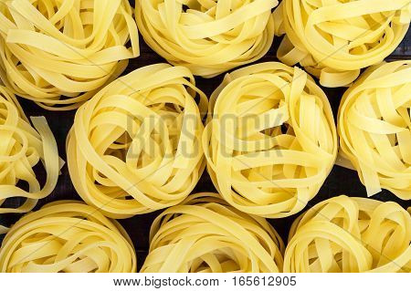 Pasta tagliatelle in the form of nests. Food background. The top view. Close-up.