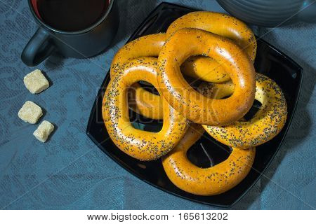 Many large bagels on a black plate and sugar on a blue tablecloth