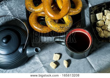 Bagels coffee cup teapot and sugar in black on a blue tablecloth. View from above