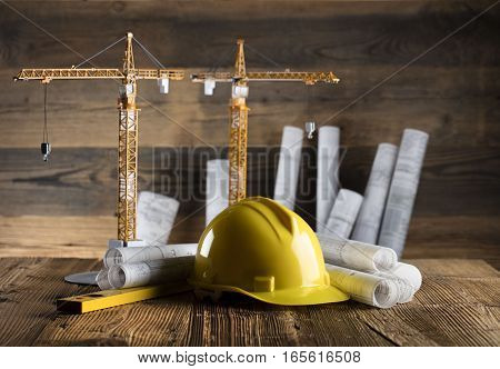 Rolls with building projects, equipment of architect: crash helmet and spirit level on wooden table.