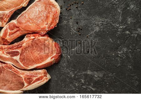 Top view raw pork chop steak on black cement background with copy space.