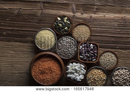 Set of different leguminous vegetable in bowls on wooden table