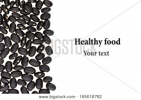 Border of black kidney beans closeup with copy space on white background. Isolated. Healthy protein food.