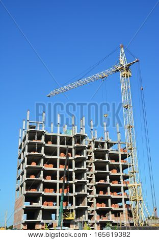 Building cranes on construction site with builders. Building high rise.Crane Construction. Tower Crane and Building Constructors on Construction Site.