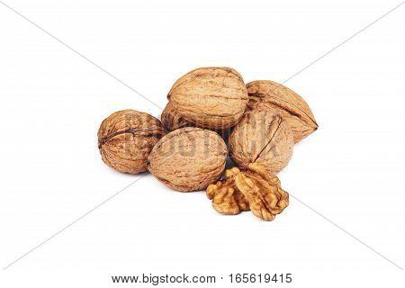Walnut kernels and whole walnuts on white background