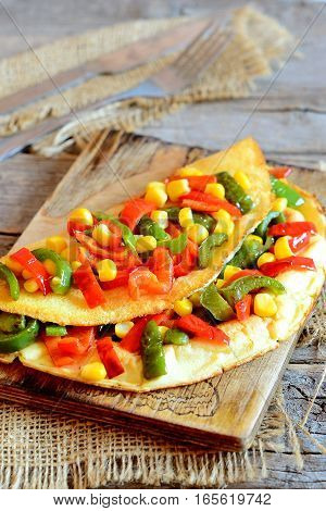 Delicious vegetable omelet on a wooden board. Fried omelet stuffed with red and green bell peppers and corn. Easy vegetarian breakfast omelet recipe. Vintage style. Closeup