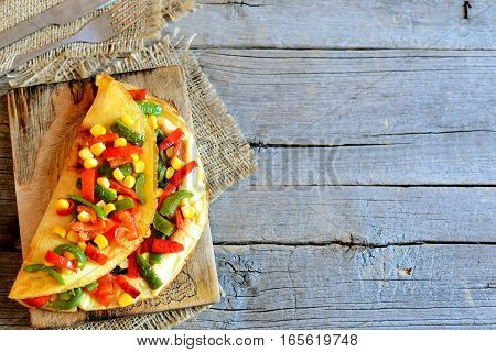 Homemade vegetable stuffed omelette on wooden background with copy space for text. Eggs omelette stuffed with red and green bell peppers and canned corn. Fork, knife, burlap textile on table. Top view