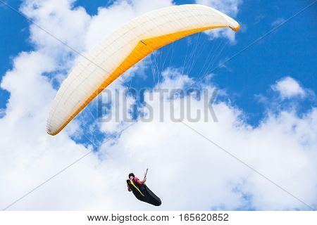 Amateur paraglider flying in blue cloudy sky