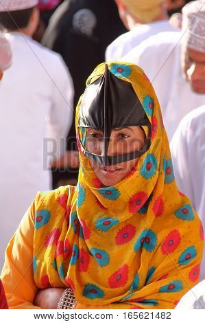 NIZWA, OMAN - FEBRUARY 3, 2012: Portrait of a bedouin Omani woman traditionally dressed attending the Goat Market in Nizwa