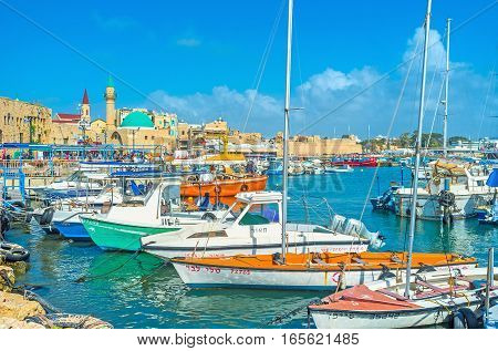 ACRE ISRAEL - FEBRUARY 20 2016: The yachts in the medieval port of Akko named HaDayagim with the green domed Sinan Basha Sea Mosque on February 20 in Acre.