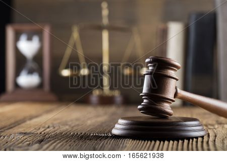 Law theme, gavel and other justice symbols on wooden table