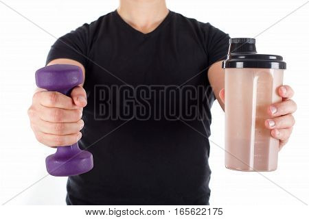 Close up picture of a young man holding a dumbbell and a shake